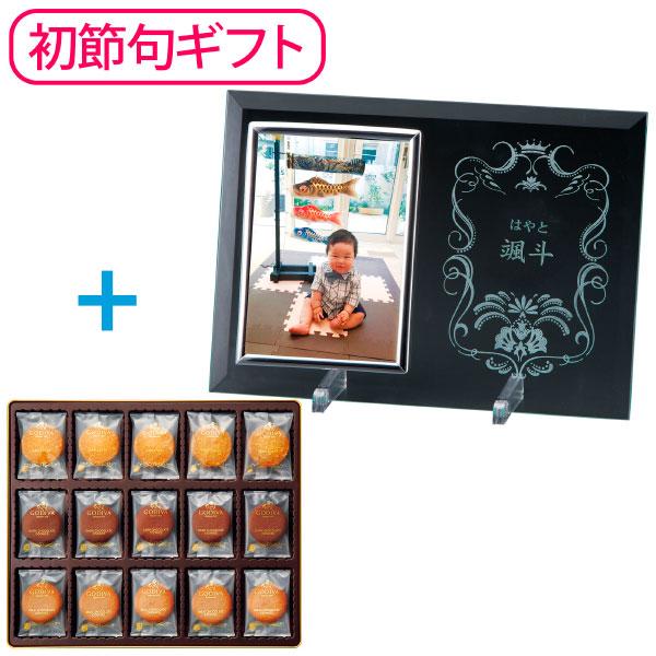 【期間限定販売】2019年7月25日まで販売 ■内容:フォトフレーム×1、クッキー(ミルクチョコレート・ダークチョコレート)×各20、クッキー(サブレノア)×15 格調高いガラスのフォトフレームと、ゴディバのスイーツをセットにして初節句の記念に。 ガラスのフォトフレームに、お子さまのお名前をレーザーでお入れします。 透明なガラスに彫られた、王冠と花をモチーフにした動きのあるデザインが、お子さまのお名前を美しく彩り、特別なギフト感をさらに際立たせます。 家族やお客様が集まるリビングのアクセントとして飾ったり、デスクに飾ったり、初節句の喜びをずっと身近に感じていただける特別なギフトです。 セットにはゴディバのクッキーアソートメントをご用意。ミルクチョコレートをほんのりココアが香るラングドシャ生地でサンドした「ミルクチョコレート」と、ココア入りラングドシャ生地に、ダークチョコレートをサンドした「ダークチョコレート」、香ばしいプラリネチョコレートと、刻んだヘーゼルナッツをサブレ生地にたっぷり練りこんだ「サブレノア」のアソートメントです。 <ゴディバ> ゴディバは、90年以上にわたりベルギーチョコレートの伝統に貢献し、世界中で愛されている高級チョコレートのリーディングブランドです。 ■配送のご注意 ●名入れメーカーより直送しますので、ほかの商品とは別便で届きます。 ●ご注文を受けてから作りますので、お届けまでに15日ほどお時間をいただきます。■フォトフレーム=化粧箱入:220×295×25mm、クッキー=化粧缶入:278×325×50mm ■内容:フォトフレーム200×2
